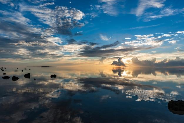 Herrlicher sonnenaufgang, bunte wolken, die sich wie ein spiegel im glatten meer spiegeln. hatoma-insel am horizont.