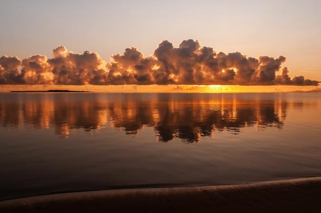 Herrlicher sonnenaufgang mit bunten, flauschigen wolken am horizont, die sich wie ein spiegel über den glatten ozean reflektieren