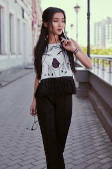 Herrliches asiatisches kleid der frau in mode, das entlang helle straße geht