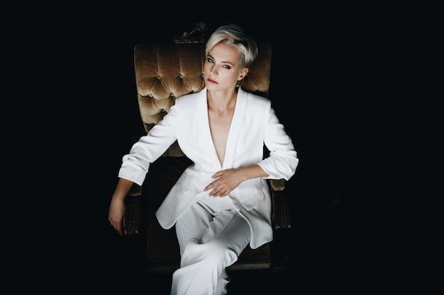Herrliches blondes mode-modell im weißen anzug sitzt auf einem weichen lehnsessel