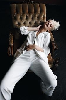 Herrliches blondes mode-modell sitzt im weißen anzug auf einem weichen lehnsessel