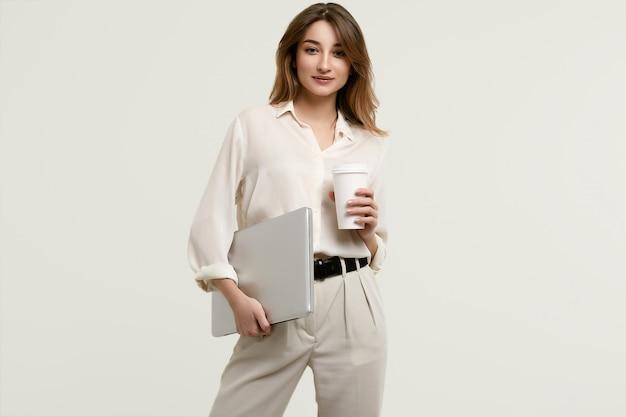 Herrliches brunettemodell in der weißen kleidung mit laptop und kaffee
