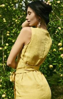 Herrliches gelbes kleid der brunettefrau in mode im apfelgarten