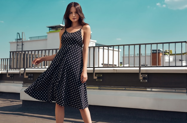 Herrliches helles kleid des brunette in mode, das auf dem dach eines gebäudes aufwirft Premium Fotos