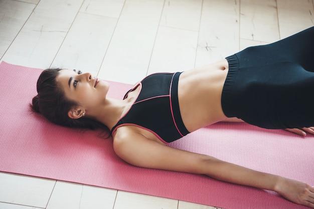 Herrliches junges kaukasisches mädchen, das sich auf einem yogateppich auf dem boden erstreckt, der aktivkleidung zu hause trägt