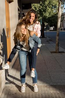 Herrliches junges mädchen, das piggyback ihrer freundin auf bürgersteig gibt
