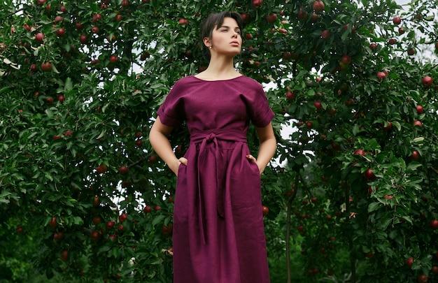 Herrliches klassisches kleid der brunettefrau in mode im apfelgarten