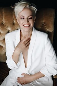 Herrliches lächelndes blondes mode-modell sitzt im weißen anzug auf einem weichen lehnsessel