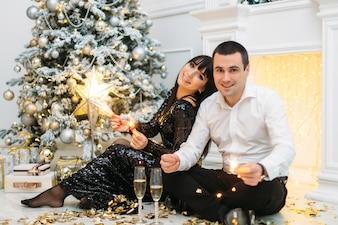 Herrliches Paar hält Bengal-Feuer, die vor einem glänzenden Weihnachtsbaum stehen