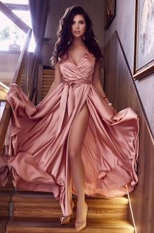Herrliches sinnliches rosakleid des brunettemodells in mode nahe der treppe