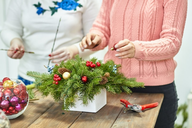 Hersteller von weihnachtsdekor mit ihren eigenen händen. weihnachtsbox mit zweigen für den urlaub. das neujahrsfest. meisterklasse für dekorative ornamente