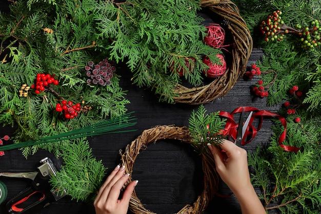 Hersteller von weihnachtsdekoration mit eigenen händen. weihnachtskranz für den urlaub. die neujahrsfeier. meisterkurs zur herstellung von dekorativen ornamenten. ansicht von oben. flaches neues jahr