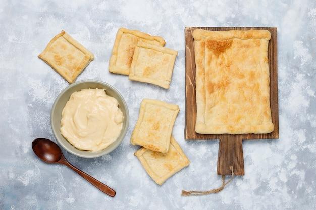 Herstellung des frischen köstlichen blätterteigs mit sahne auf konkreter, draufsicht