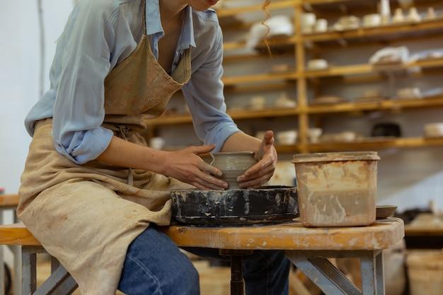 Herstellung eines neuen topfes. hart arbeitendes dünnes mädchen, das ihre erfahrung in der töpferei zeigt, während sie große tiefe töpfe produziert