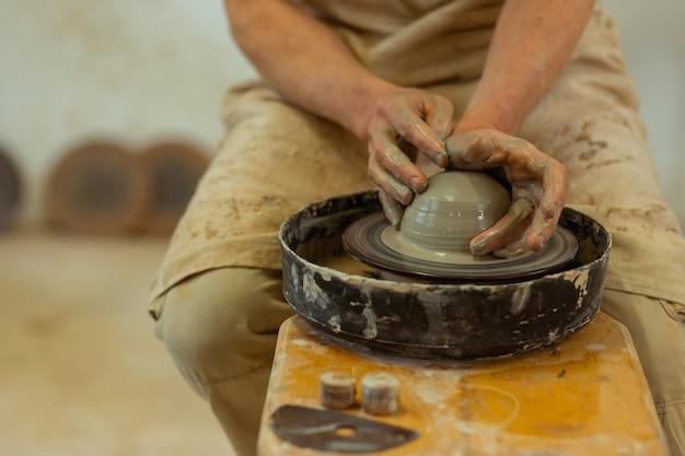 Herstellung neuer töpfe. qualifizierter starker mann mit nassen, schmutzigen händen, der auf einer töpferscheibe produziert, während er im studio bleibt