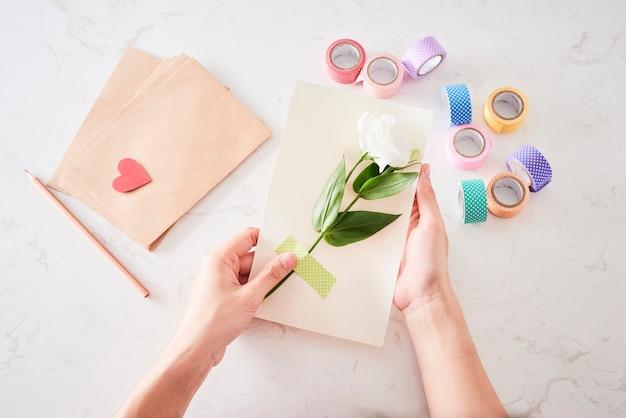 Herstellung von dekorationen oder grußkarten. papierstreifen, blume, schere