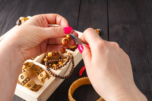 Herstellung von handgefertigtem schmuck. box mit perlen auf altem holztisch.