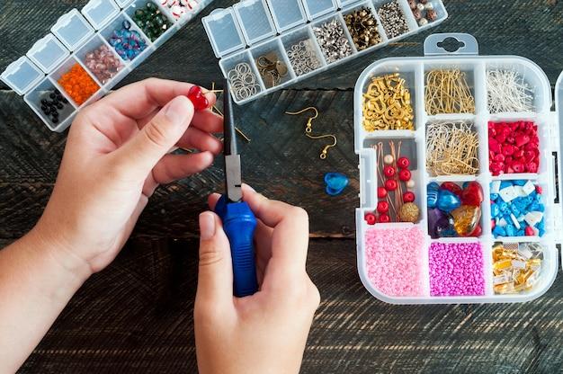 Herstellung von handgefertigtem schmuck. box mit perlen und glasherzen auf altem hölzernen hintergrund