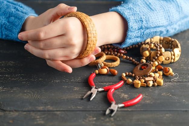 Herstellung von handgefertigtem schmuck. box mit perlen und glasherzen auf alter holzoberfläche. handgemachtes zubehör