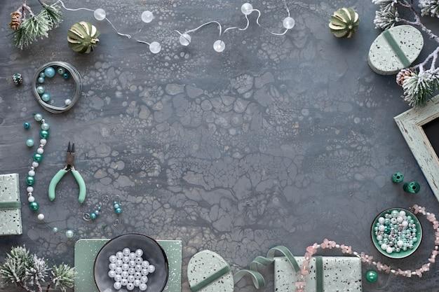 Herstellung von handgefertigtem schmuck für freunde als weihnachtsgeschenk. flach lag auf dunklem strukturiertem hintergrund mit kopierraum.