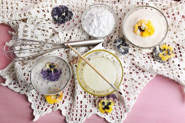 Herstellung von kandierten violetten blüten mit eiweiß und zucker auf holzfarbe