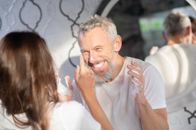 Herumalbern. ein mann und eine frau, die kindliche dinge mit rasierschaum tun