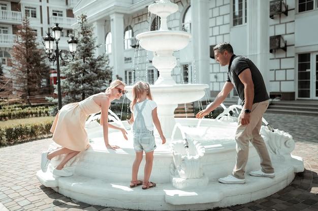 Herumalbern. glückliche familie, die spaß beim spielen mit wasserspritzern in der nähe des schönen brunnens hat.