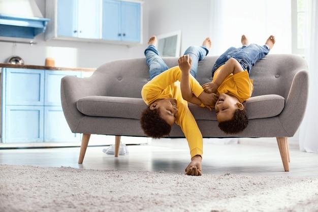 Herumspielen. fröhliche kleine brüder, die kopfüber auf dem sofa liegen und sich gegenseitig kitzeln, während sie glücklich lachen