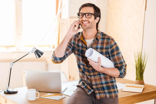 Hervorragende ergebnisse seiner arbeit. glücklicher junger mann, der blaupause hält und mit dem handy spricht, während er sich an seinem arbeitsplatz lehnt