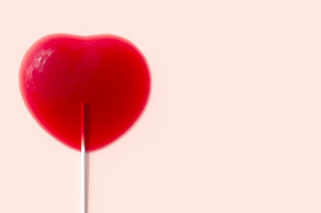 Hervorragende rote herzform der schmelze des süßigkeitenlutschers auf rosa hintergrund. 3d-rendering. minimale valentinstag-konzept-idee.