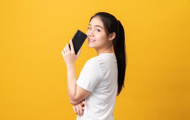 Hervorragende schöne asiatische frau, die smartphone hält und nachricht auf hellgelbem hintergrund tippt