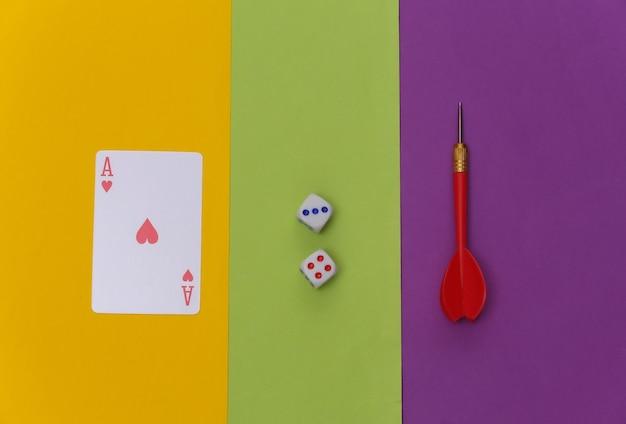 Herz-ass, darts und würfel auf farbigem hintergrund. ansicht von oben