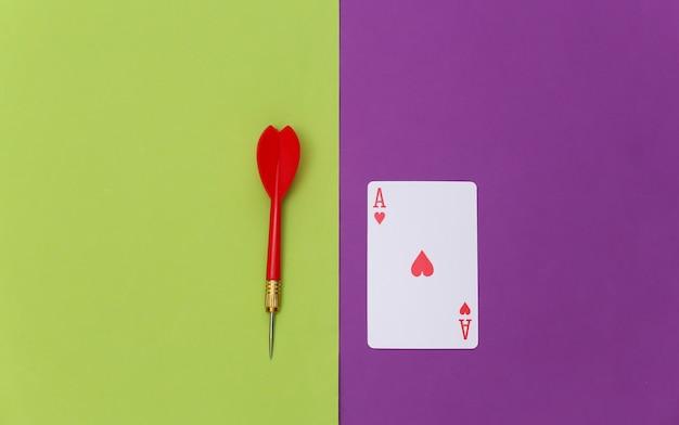 Herz-ass und darts auf lila grünem hintergrund. ansicht von oben