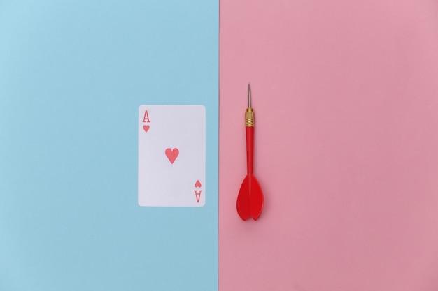 Herz-ass und pfeile auf rosa blauem pastellhintergrund. ansicht von oben