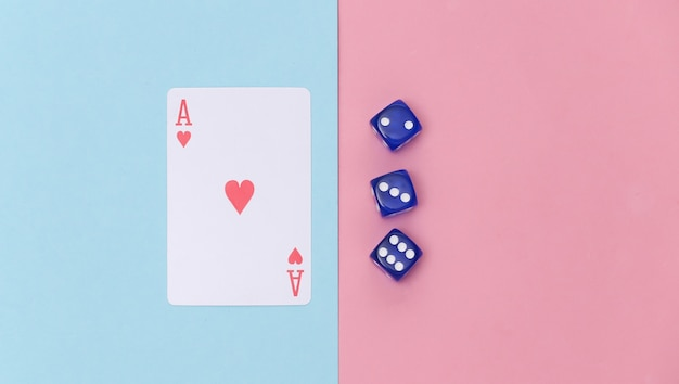 Herz-ass und würfel auf rosa blauem pastellhintergrund. ansicht von oben