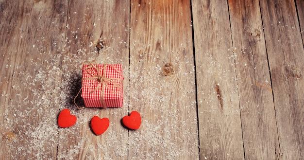 Herz auf einem hölzernen hintergrund mit schnee. valentinstag. valentinstag grußkarte.