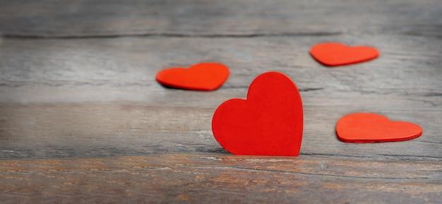 Herz auf einem hölzernen hintergrund. rote herzen auf dunklem hölzernem hintergrund