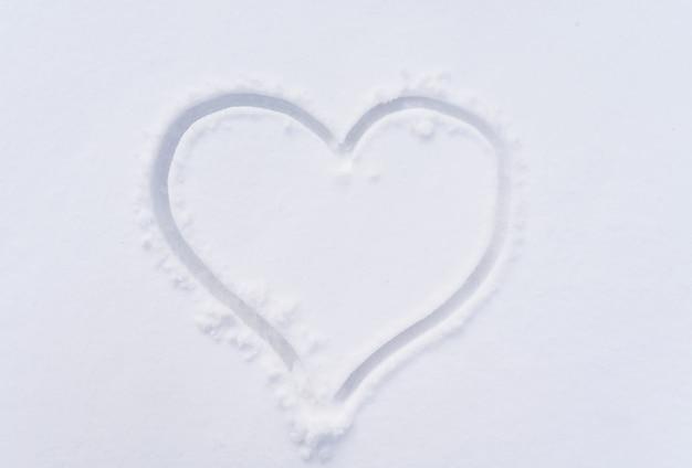 Herz auf weißem schnee. wintersymbol der liebe am valentinstag. romantik und feier.