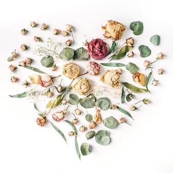 Herz aus beigen rosen und grünen blättern auf weißem hintergrund. valentinstag hintergrund. flache lage, draufsicht