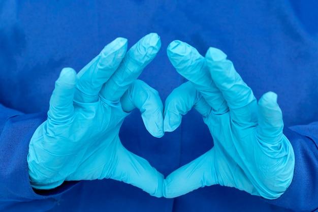 Herz aus blauen medizinischen handschuhen. sterilität, hygiene, labortests