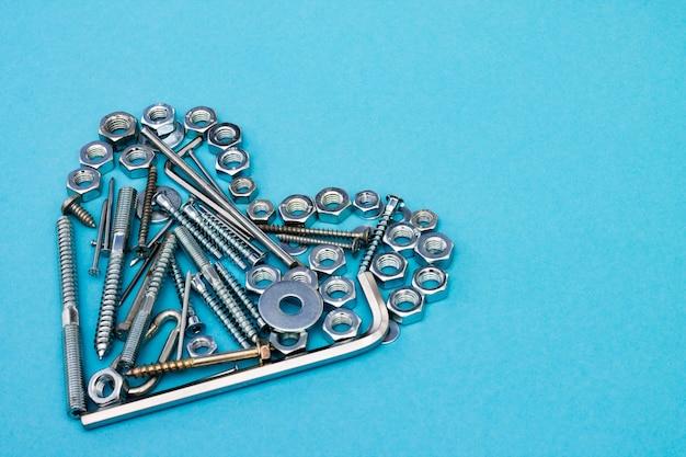 Herz aus bolzen, muttern, schraubenschlüsseln und anderen bauwerkzeugen auf blauem grund. copyspace