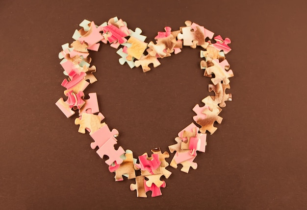 Herz aus dem puzzle auf dem braunen hintergrund gemacht.