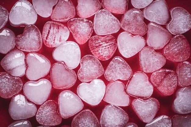 Herz aus eis auf rotem grund. romantische karte mit gefrorenen herzen.