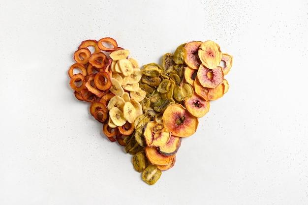 Herz aus getrockneten geschnittenen pflaumen-kiwi-pfirsich-chips auf weiß