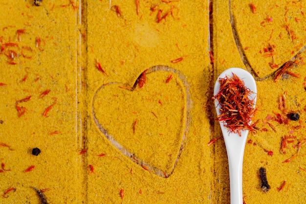 Herz aus gewürzen und gewürzen. weißer löffel mit safran auf curry