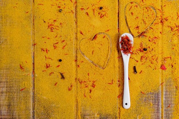 Herz aus gewürzen und gewürzen. weißer löffel mit safran auf curryhintergrund.