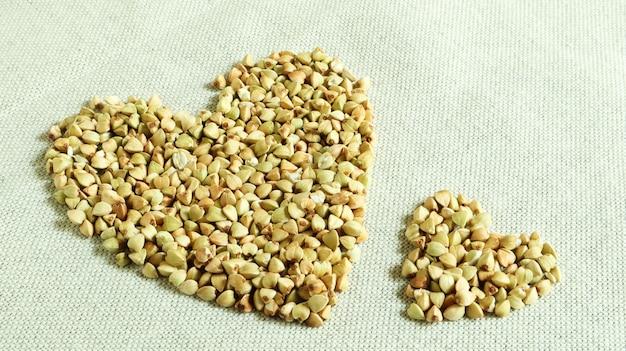 Herz aus grünem buchweizen. symbol der liebe und gesundheit. tolles essen. gesunde grütze. bio roh