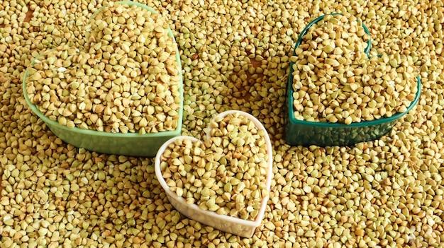 Herz aus grünem buchweizen. symbol der liebe und gesundheit. tolles essen. gesunde grütze. organisches rohes, nicht gebratenes vegetarisches essen. das konzept einer gesunden, ausgewogenen und diätetischen ernährung. platz kopieren.