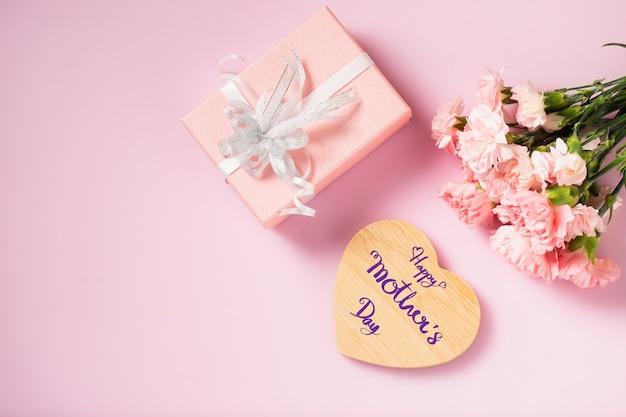 Herz aus holz für eine glückliche muttertagsnachricht mit geschenkbox und nelkenblumen, muttertag und valentinstag