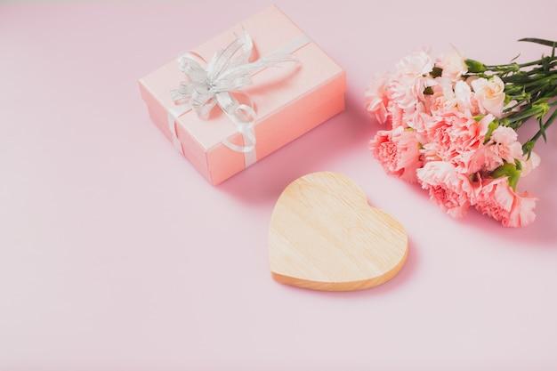 Herz aus holz leer für nachricht mit geschenkbox und nelkenblumen, muttertag und valentinstag